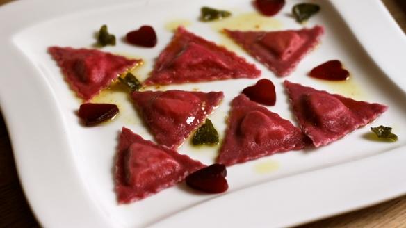 ravioli iz testa z rdečo peso, polnjeni z ovčjo sirarsko skuto z artičokami in preliti z na maslu pocvrtim žajbljem
