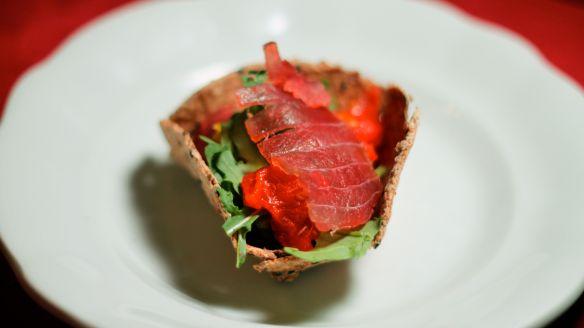 kreker z ovsenimi kosmiči, pečeno/sušenimi paradižniki, rukolo, pinjolami in na domači brjači v češnjevem dimu hladno dimljeno tuno